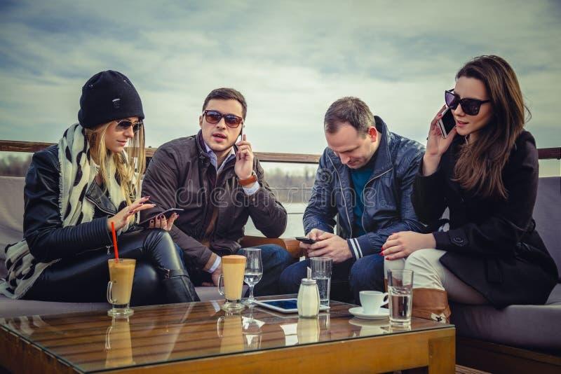 En grupp människor som använder mobiltelefonen arkivfoto