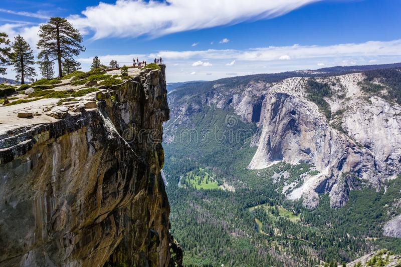 En grupp människor som besöker Taft punkt, en populär utsiktpunkt; El Capitan, Yosemite dal och Merced flod som är synliga på rät royaltyfri bild