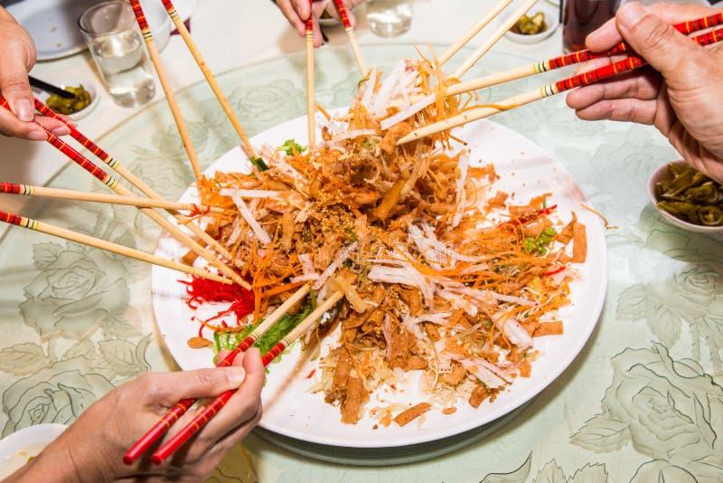 En grupp människor som blandar och kastar den Yee Sang maträtten med kotlett, klibbar Yee Sang är en populär läckerhet som tas un arkivfoto