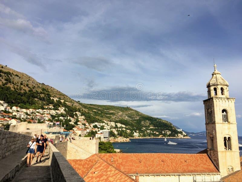 En grupp människor som går längs Dubrovniks väggar med Adriatiska havet och lyssnar i bakgrunden i Dubrovnik, Kroatien arkivbild