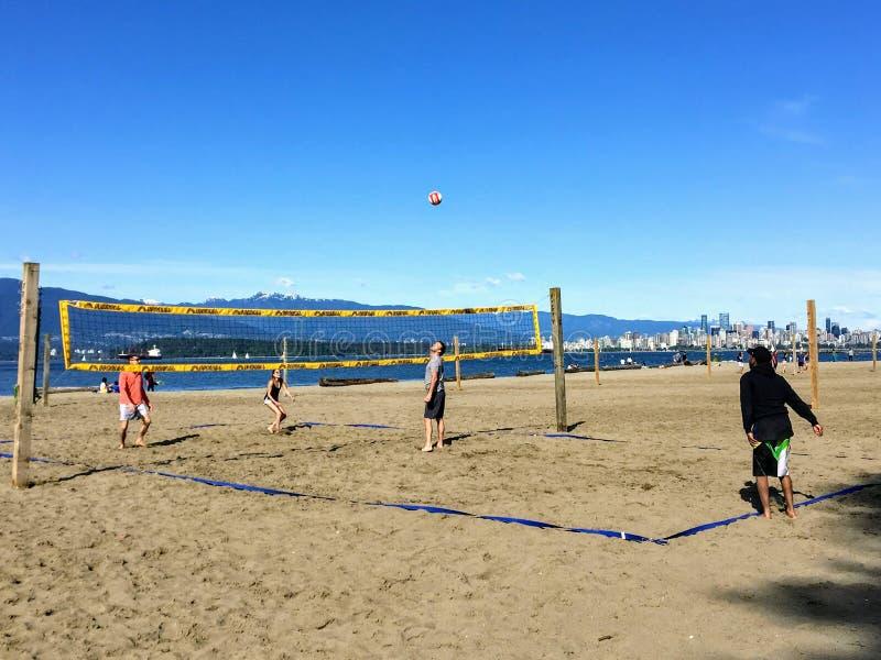 En grupp m?nniskor som spelar strandvolleyboll p? en h?rlig solig dag l?ngs de sandiga str?nderna av spanska banker, i Vancouver, arkivfoton