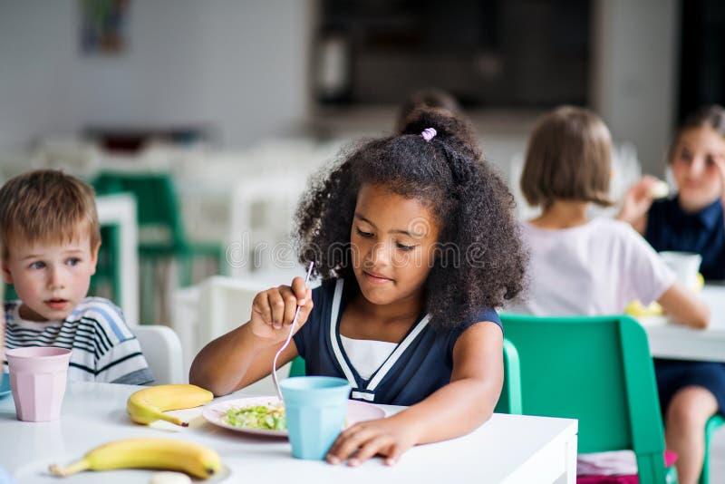 En grupp trevliga små skolbarn i matsalen, som äter lunch arkivfoto