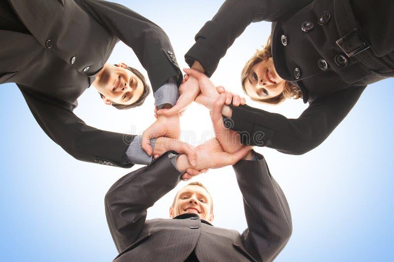 En grupphandskakning mellan tre affärspersoner royaltyfria bilder