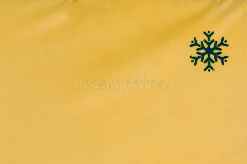En gul bakgrund med en sn?flinga royaltyfria bilder