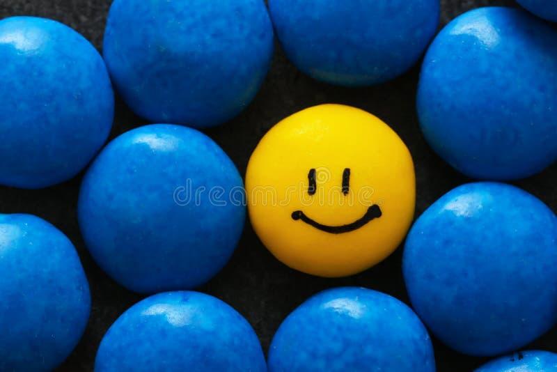 En gul droppe med den målade lyckliga framsidan royaltyfria foton