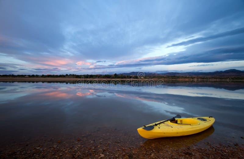 En gul kajak med en åra på kusten av en sjö på soluppgång fotografering för bildbyråer