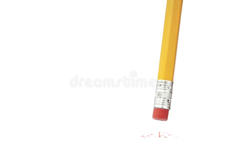 En gul penna raderar något, med gummibitar på vit bakgrund Kopiera utrymme Gul penna med rött royaltyfri fotografi