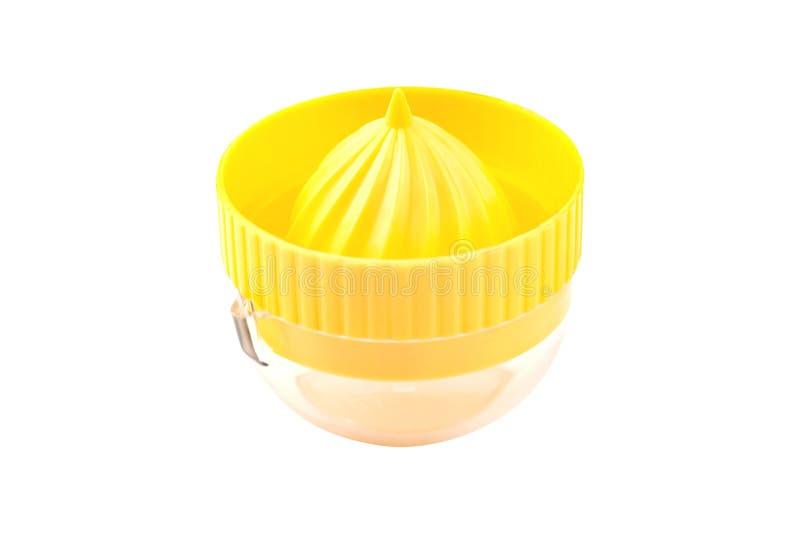 En gul plastjuicer med genomskinlig tank för att framställa färsk naturlig juice av olika frukter och grönsaker som är isolerade arkivbild