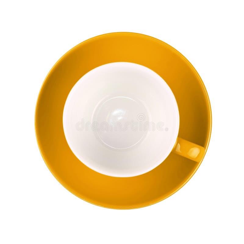 En gul tom kaffe- eller tekopp med tefatet som isoleras på vit bakgrund royaltyfri fotografi