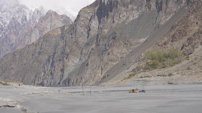 En gul traktor som gräver sand i den Hunza floden royaltyfria bilder