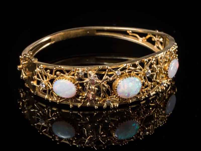 En guld- armring med tre opalgemstones royaltyfria foton
