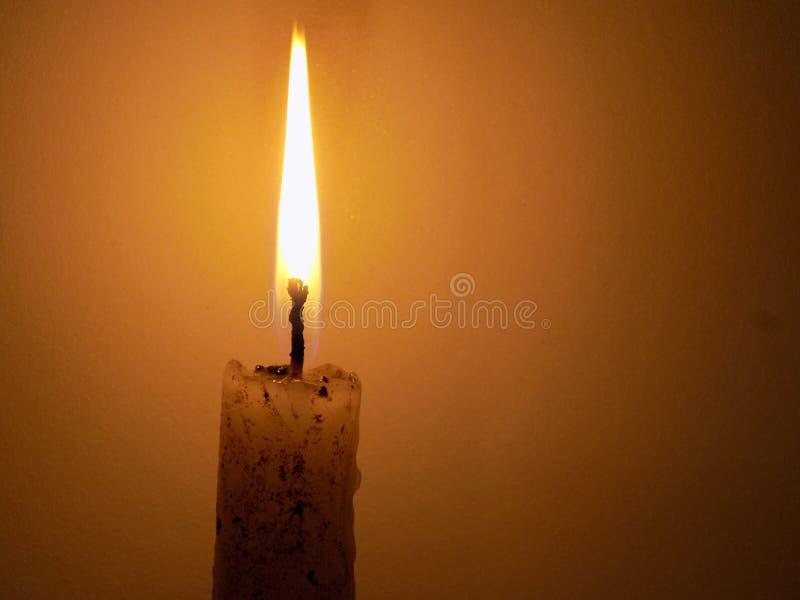 En guld- flamma i en stearinljus fotografering för bildbyråer