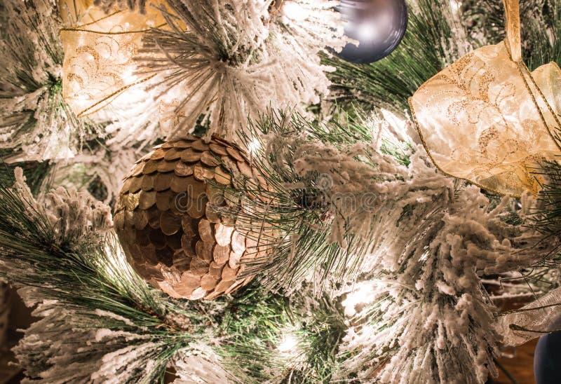 En guld- julprydnad på en flockas julgran arkivbilder