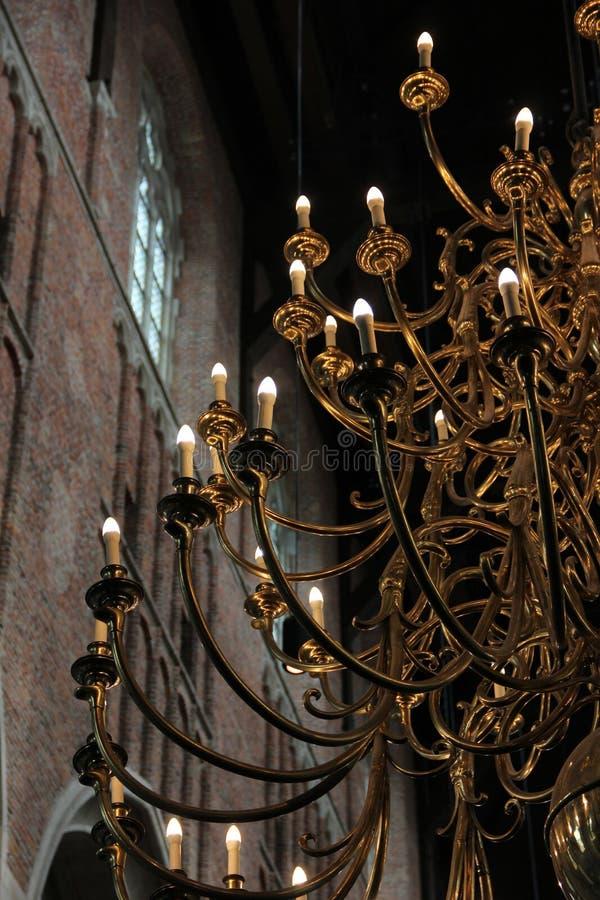 En guld- ljuskrona inom en kyrka arkivfoton