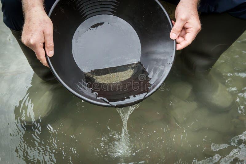 En guld- panna med vatten och sand i den arkivbilder