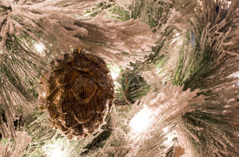 En guld- pineconejulprydnad på en flockas julgran royaltyfri fotografi