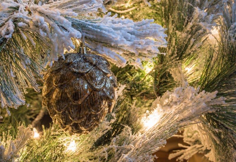 En guld- pineconejulprydnad på en flockas julgran royaltyfria bilder