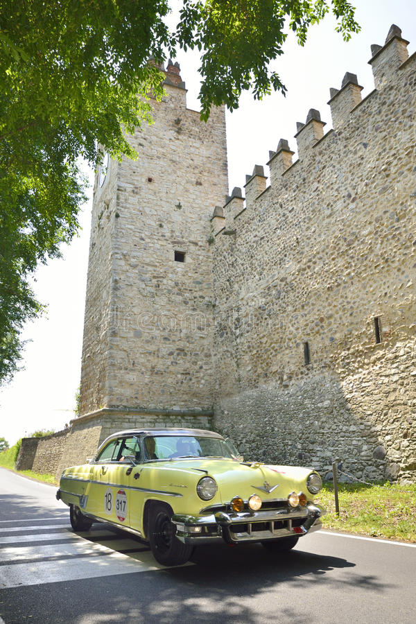 En gulingLincoln Capri Sport Coupe tagande särar till Miglia det klassiska billoppet 1000 arkivbild