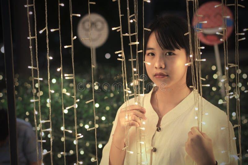 En gullig asiatisk flicka som ser ledd lighting arkivfoton