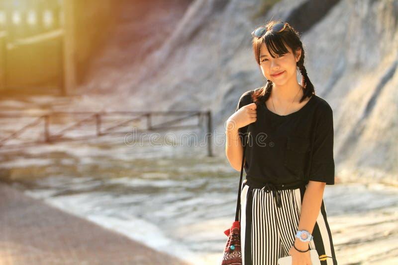 En gullig asiatisk flicka står i en olik position arkivfoton