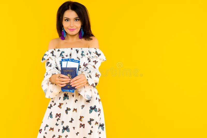 En gullig asiatisk kvinna i en siden- klänning med fjärilar rymmer ett pass och flygbiljetter på en gul bakgrund royaltyfri bild