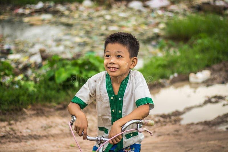 En gullig Burmese pojkeframsida i en lantlig by utanför staden royaltyfria foton