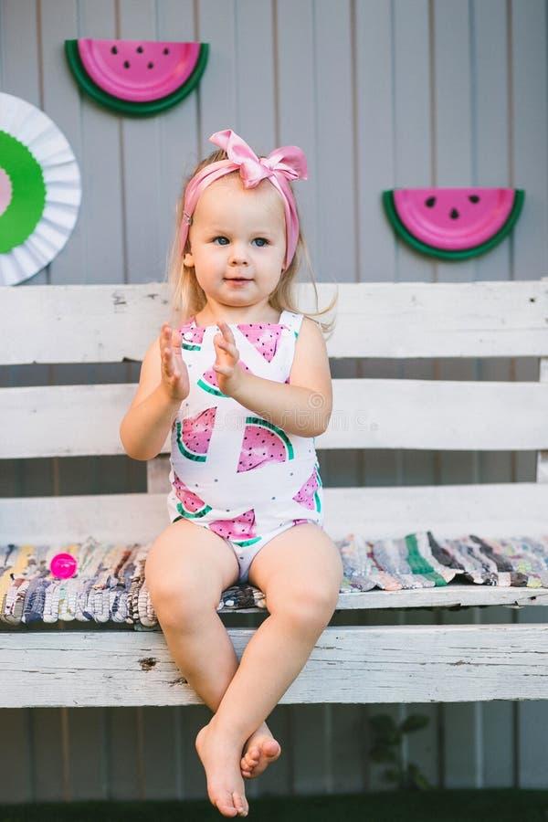 En gullig liten flicka i en jumpsuit sitter på en trävit bänk och applåderar henne händer royaltyfri fotografi