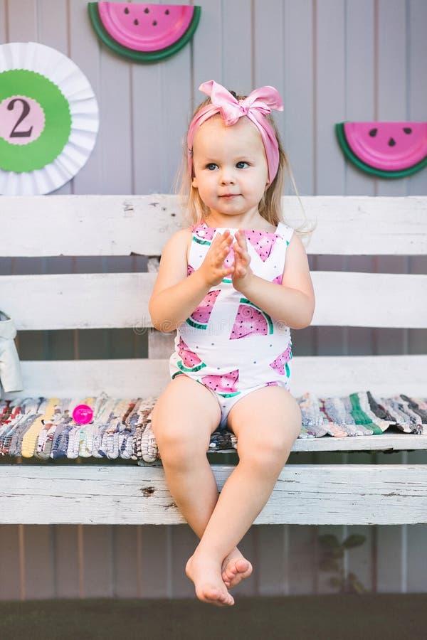 En gullig liten flicka i en jumpsuit sitter på en trävit bänk och applåderar henne händer royaltyfri bild