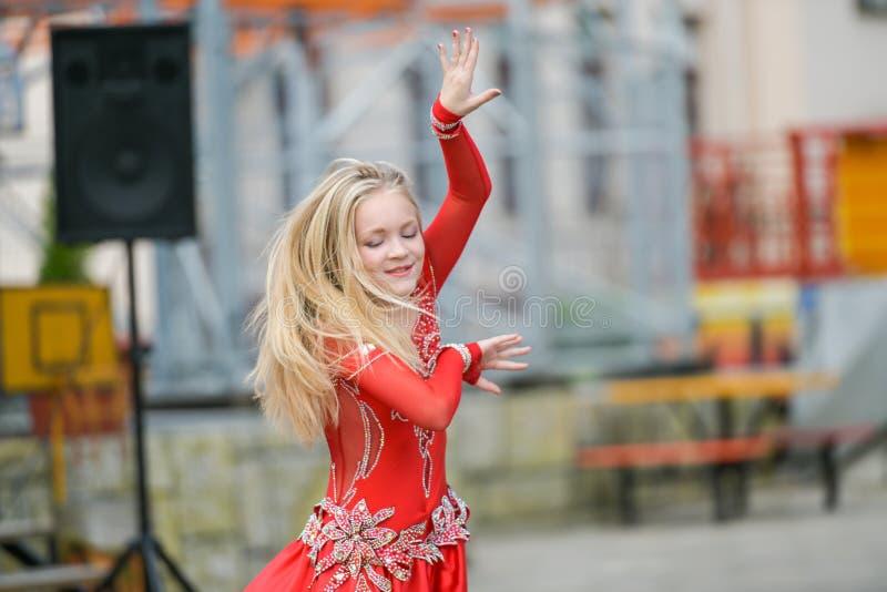 En gullig liten flicka i en röd dräkt dansar på gatan Flicka i dansgruppen Behandla som ett barn flickan lär dans Showdans till royaltyfria foton
