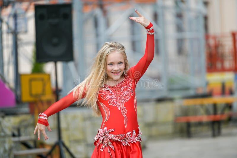 En gullig liten flicka i en röd dräkt dansar på gatan Flicka i dansgruppen Behandla som ett barn flickan lär dans Showdans till fotografering för bildbyråer