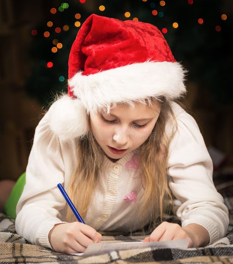 En gullig liten flicka med entusiasm skrivar ett brev till jultomten arkivbild