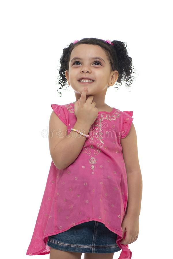 En gullig liten flicka som ser upp, tänka som söker för idé som isoleras på vit bakgrund royaltyfri bild