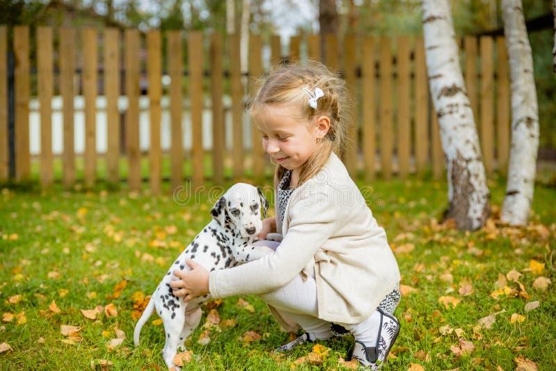 En gullig liten litet barnflicka som ger en kram till hennes hund, Dalmatian valp, nedgångsäsong i en trädgård, gräsmatta med hös arkivbild