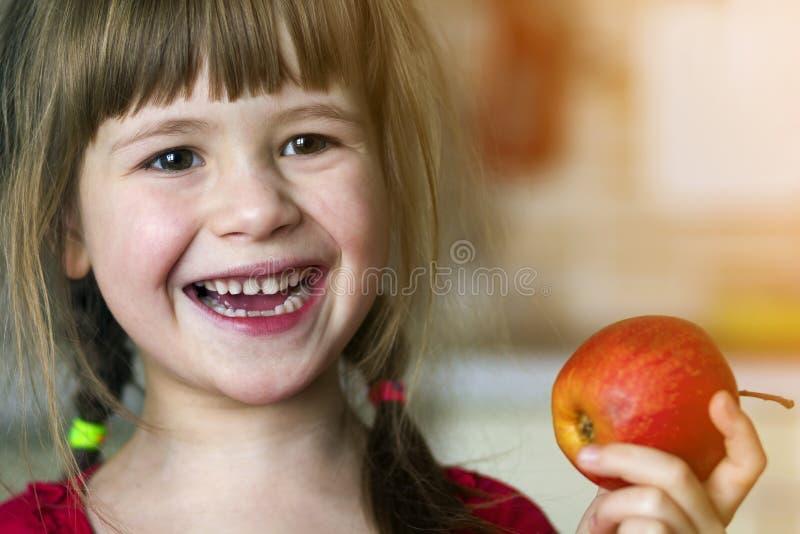 En gullig liten lockig tandlös flicka ler och rymmer ett rött äpple Ståenden av ett lyckligt behandla som ett barn äta ett rött ä fotografering för bildbyråer