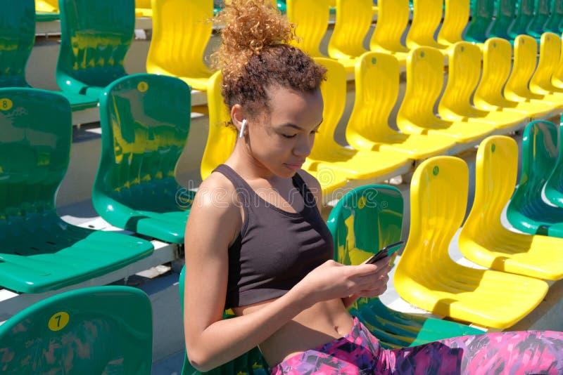 En gullig mörkhyad flicka i en svart T-tröja med en vit trådlös skalm i hennes öra ser in i telefonen och sitter på en stol för fotografering för bildbyråer