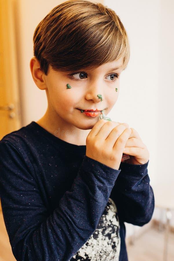 En gullig pojke målar hans framsida med ätbar färgkräm royaltyfri foto