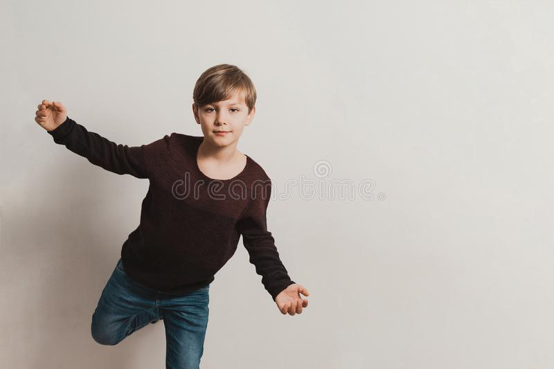 En gullig pojke vid den vita väggen, brun sweater, jeans royaltyfria bilder
