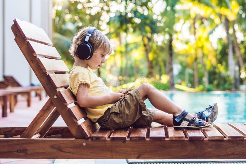 En gullig pys använder en smartphone och hörlurar som ligger på en deckchair vid pölen primär utbildning, kamratskap arkivbild