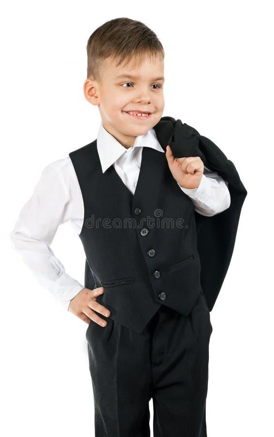 En gullig pys i en vit skjorta och svartwaistcoat är holdin royaltyfri foto