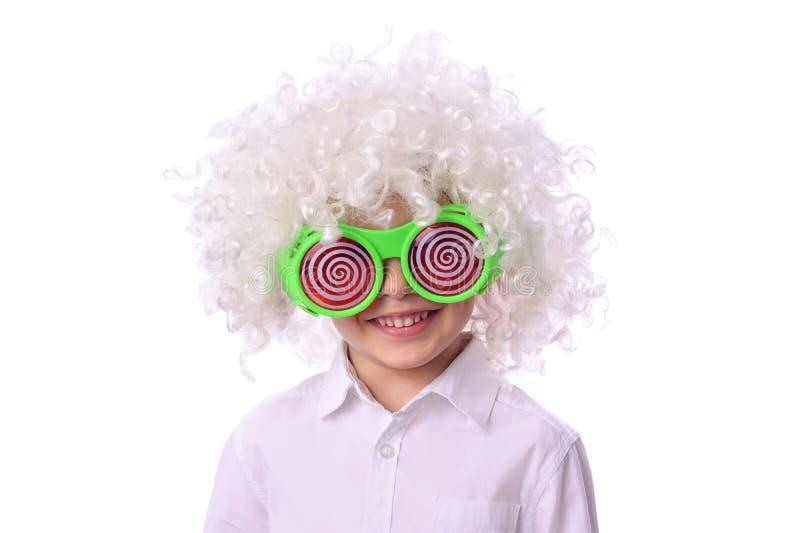 En gullig rolig pojke i den vita peruken för clown och gröna exponeringsglas som isoleras på vit arkivfoto