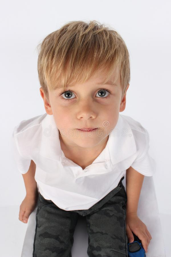 En gullig stilig preteen pojke som innocently sitter och uppriktigt och ser royaltyfria bilder