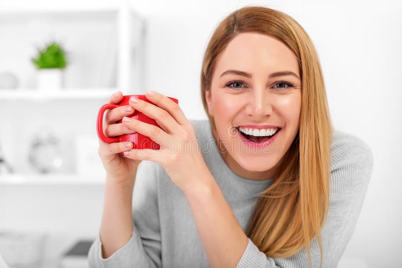En gullig ung kvinna rymmer ett rött koppsammanträde på en tabell i ett vitt kontor söt kopp för giffel för bakgrundsavbrottskaff fotografering för bildbyråer