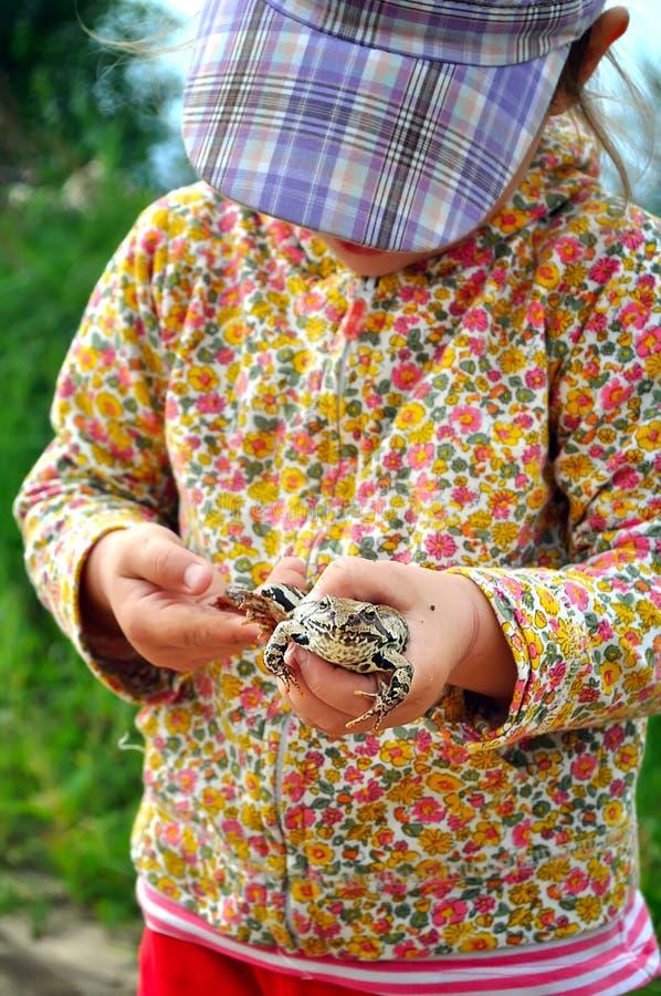 En gullig ungt barnflicka som rymmer en grodapadda, i händer och att skratta arkivbilder