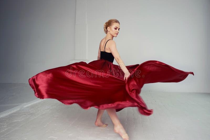 En gymnast i en mörk överkant och en röd siden- kjol Färgen av passion, av agression tango Plast- kropp, airiness arkivfoton
