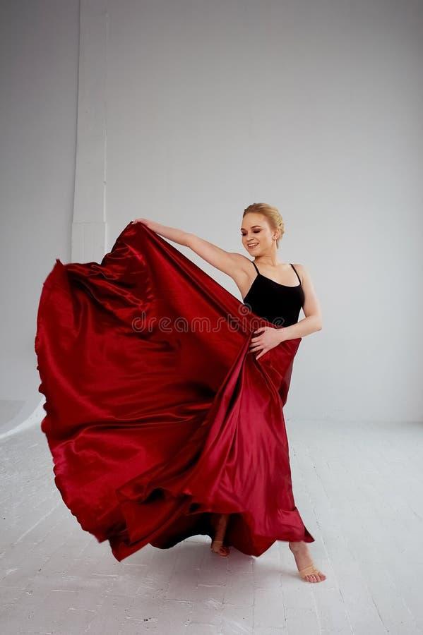 En gymnast i en m?rk ?verkant och en r?d siden- kjol F?rgen av passion, av agression tango Plast- kropp, airiness royaltyfri bild