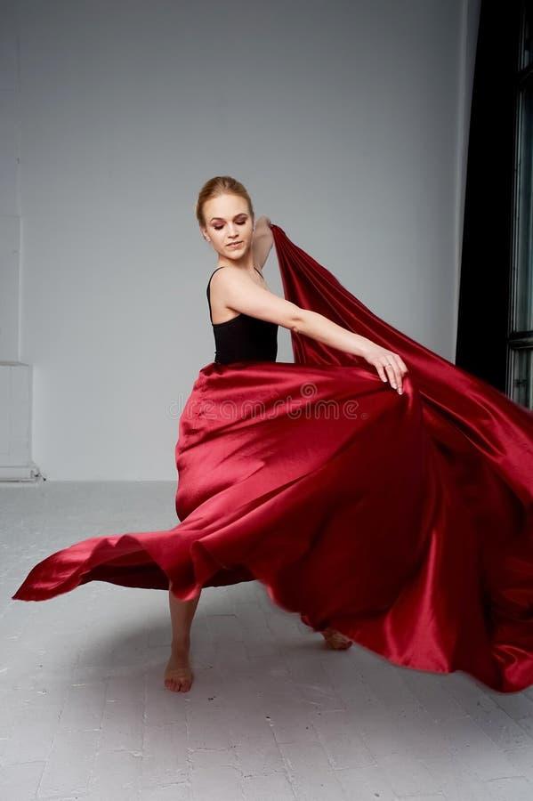En gymnast i en m?rk ?verkant och en r?d siden- kjol F?rgen av passion, av agression tango Plast- kropp, airiness fotografering för bildbyråer