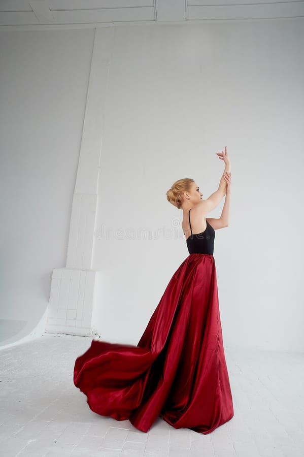 En gymnast i en m?rk ?verkant och en r?d siden- kjol F?rgen av passion, av agression tango Plast- kropp, airiness royaltyfri foto