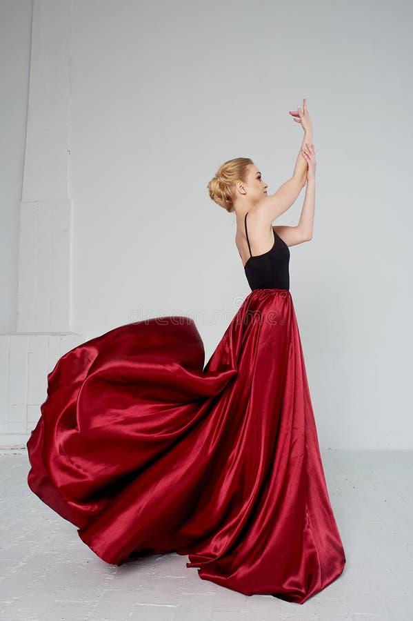 En gymnast i en m?rk ?verkant och en r?d siden- kjol F?rgen av passion, av agression tango Plast- kropp, airiness royaltyfri fotografi
