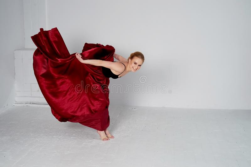 En gymnast i en m?rk ?verkant och en r?d siden- kjol F?rgen av passion, av agression tango Plast- kropp, airiness arkivbild