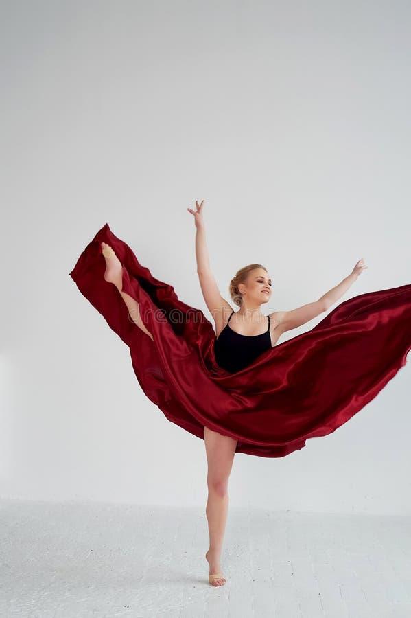 En gymnast i en m?rk ?verkant och en r?d siden- kjol F?rgen av passion, av agression tango Plast- kropp, airiness arkivfoto